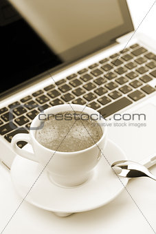 Cappuccino cup on laptop