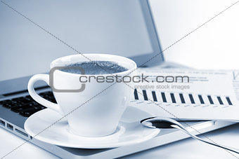 Cappuccino cup with laptop and newspaper. Toned