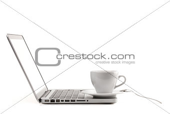 Cappuccino cup with spoon on laptop