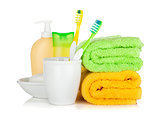 Two colorful toothbrushes, cosmetics bottles and towels