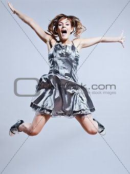 beautiful young girl with prom dress jumping screaming happy