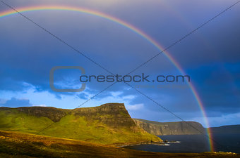 Rainbow over a dramatic coast of Scottish highlands, Isle of Sky