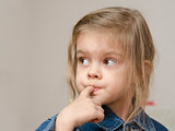 Four-year-old girl with a finger in mouth look left
