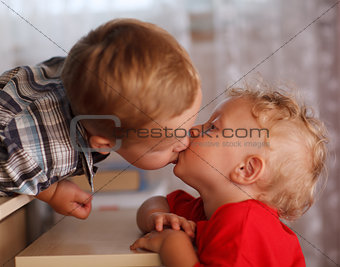Cute siblings. Two little brothers are kissing.