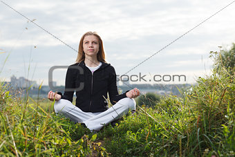 Young girl makes yoga exercises outdoors.