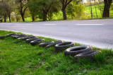 Old tyres are laid next to the empty road.