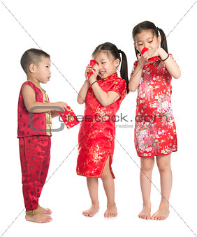 Asian children peeking into red packet