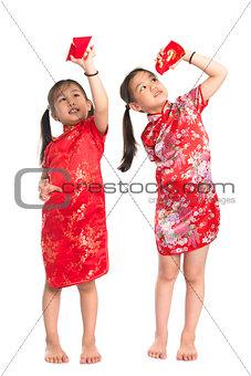 Asian girls peeking into red packet