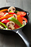 colorful vegetables in black pan ready for frying