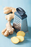 fresh ginger and grater over blue