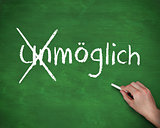 Hand crossing out the german word unmoglich