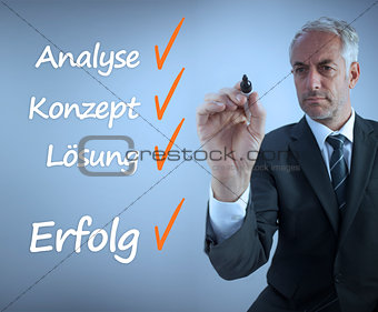 Attractive businessman writing a success checklist in german