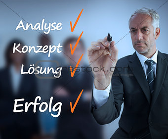 Businessman writing a success checklist in german
