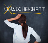 Woman looking at a chalkboard with sicherheit on it