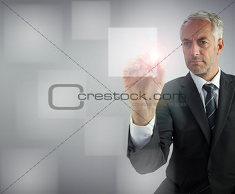 Serious businessman touching empty pane on digital screen