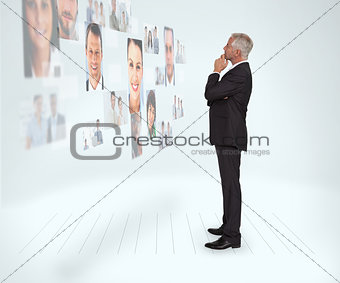 Thoughtful businessman looking at a wall covered by profile pictures