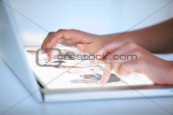 Close up of hands selecting pictures on a futuristic laptop