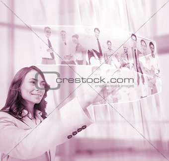Pleased businesswoman scrolling pictures on digital screen