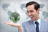 Content businessman admiring a green globe