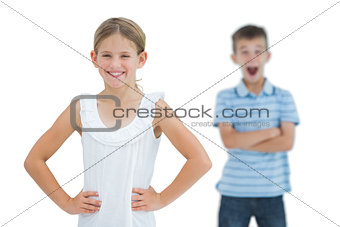 Cute young girl posing while her brother being shocked