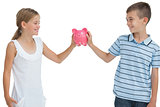 Smiling brother and sister holding piggy bank together