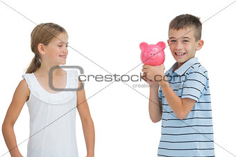 Smiling young boy holding piggy bank