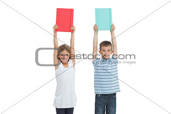 Happy brother and sister holding their notebooks above their head
