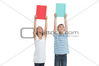 Smiling brother and sister holding their notebooks above their head