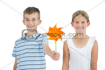 Smiling brother and sister playing with pinwheel