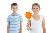 Happy brother and sister playing with pinwheel