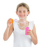 Smiling girl making bubbles