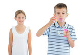 Boy making bubbles while his sister looking at him