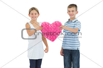 Children holding heart shaped soft toy