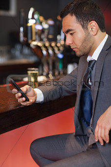 Handsome businessman sending a text while having a drink