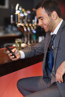 Smiling businessman sending a text while having a drink
