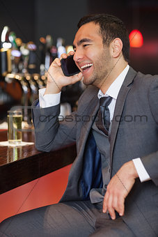 Cheerful businessman on the phone having a drink