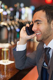 Smiling businessman on the phone having a drink