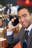 Happy businessman on the phone having a drink