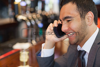 Cheerful handsome businessman on the phone having a drink