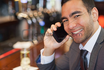 Happy handsome businessman on the phone having a drink