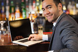 Smiling businessman working on his laptop while having a drink