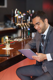 Smiling businessman working on his tablet computer