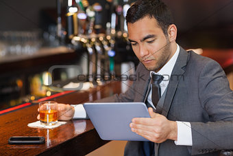 Serious businessman working on his tablet computer