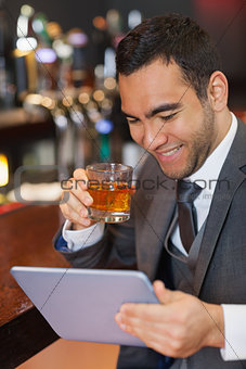 Smiling businessman working on his tablet while having a whiskey