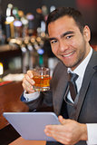 Cheerful businessman working on his tablet while having a whiskey