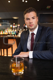 Serious businessman having a drink