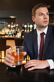 Thoughtful businessman having a drink