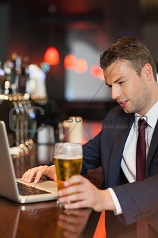 Businessman having a drink while working on his laptop