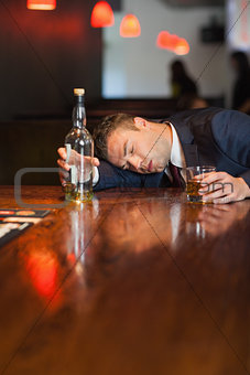 Motionless businessman holding whiskey glass lying on a counter