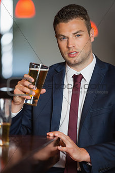 Handsome businessman having a pint